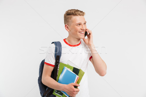 Stock photo: Image of european positive student guy wearing backpack talking