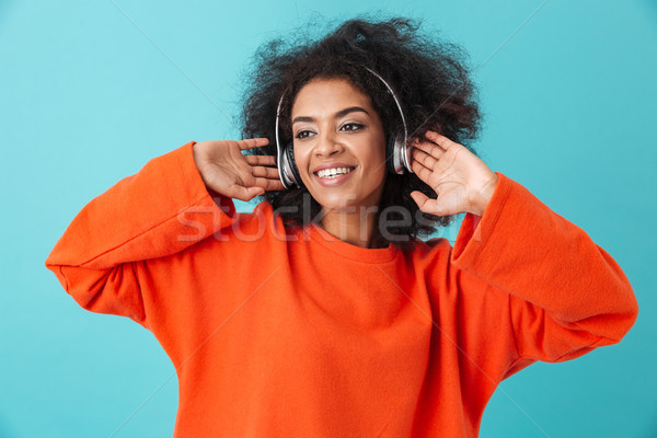 Stock photo: Pleased american woman 20s with shaggy hairdo enjoying music via