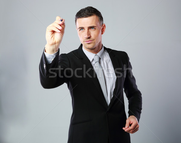 Confident businessman writes with pen at copyspace on gray background Stock photo © deandrobot