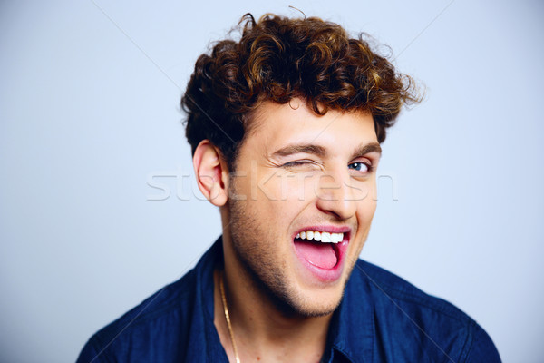 Cheerful young man winking over blue background Stock photo © deandrobot