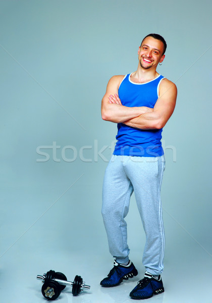 Full-length portrait of a muscular man standing with arms folded on gray background Stock photo © deandrobot
