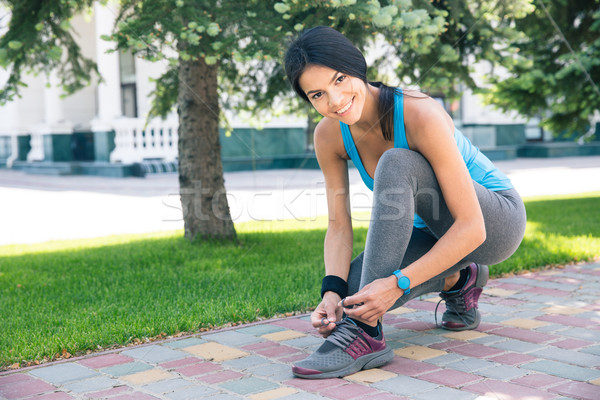 Smiling woman tying her shoelace outdoors Stock photo © deandrobot