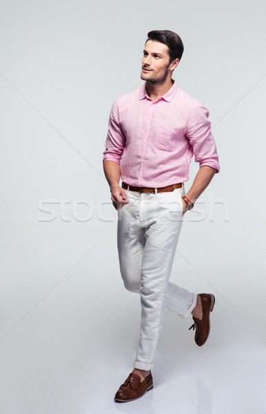 Businessman in shirt walking over gray background Stock photo © deandrobot