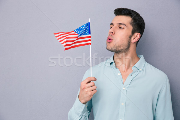 Young man blowing on US flag Stock photo © deandrobot