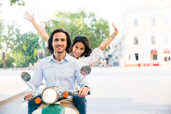 Cheerful couple riding on a scooter Stock photo © deandrobot