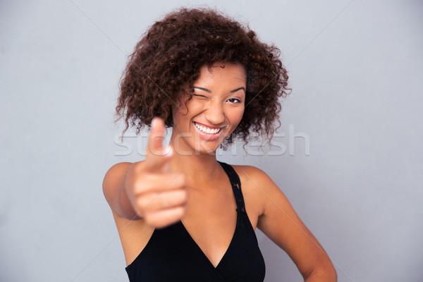 African woman showing gun gesture at camera Stock photo © deandrobot