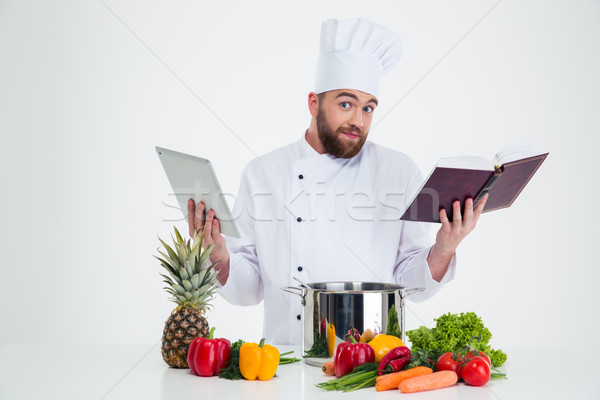 Male chef cook holding tablet computer and receipe boo Stock photo © deandrobot