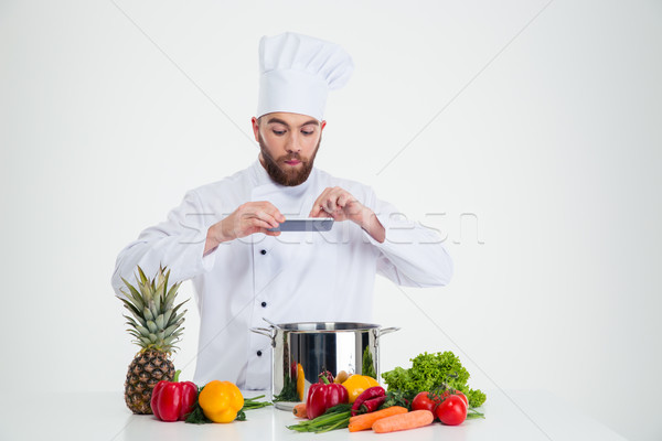 Male chef cook making photo of food Stock photo © deandrobot