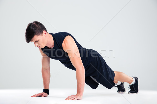 Portrait of a fitness man doing push ups Stock photo © deandrobot