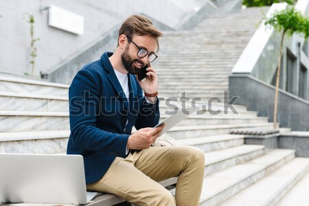 Young handsome man reading on the window sill Stock photo © deandrobot