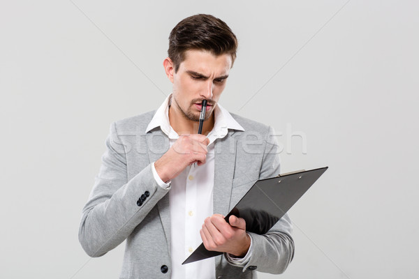 Concentrated young businessman planning and writing in clipboard Stock photo © deandrobot