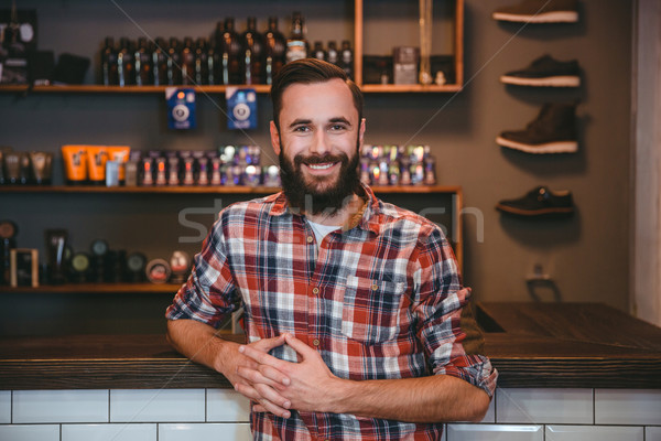 Joyful smiling bearded man posing in barbershop  Stock photo © deandrobot