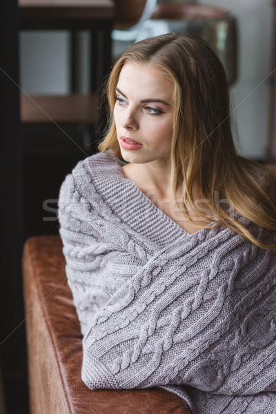 Thoughtful woman sitting on sofa wrapped in grey knitted coverlet Stock photo © deandrobot