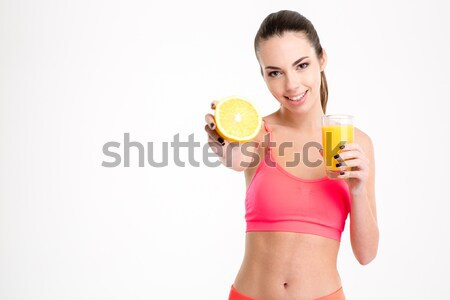 Fitness girl with orange half and glass of juice Stock photo © deandrobot
