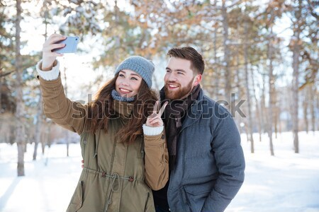 Man holding his girlfriend on hands in winter park Stock photo © deandrobot