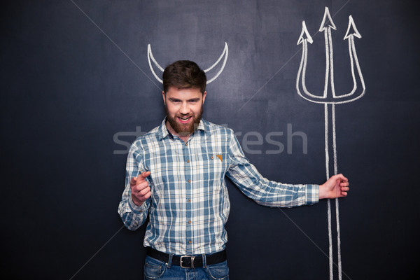 Man holding trident and pointing on you over blackboard background Stock photo © deandrobot