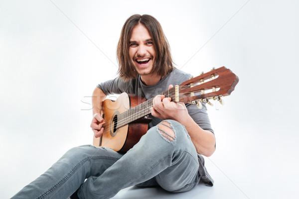 красивый мужчина длинные волосы сидят играет гитаре Сток-фото © deandrobot