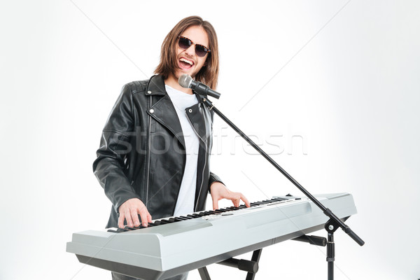 Happy attractive man singing in microphone and playing on synthesizer Stock photo © deandrobot