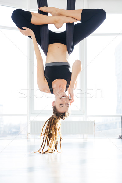 Cheerful woman doing aerial yoga and talking on mobile phone Stock photo © deandrobot