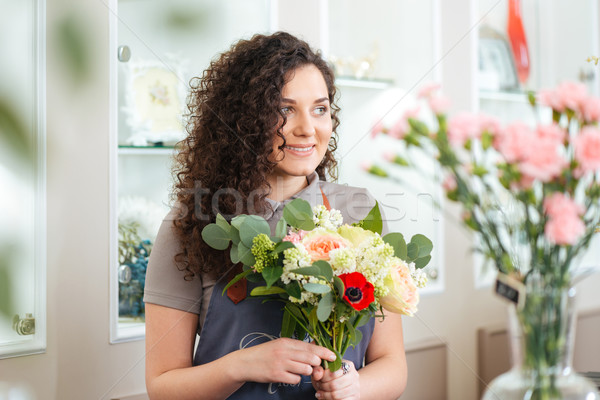 Happy woman florist working in flower shop Stock photo © deandrobot