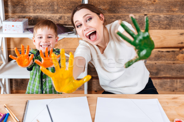 Happy mother and son showing painted hands in colorful paint  Stock photo © deandrobot