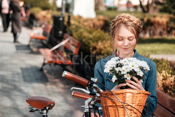 Charming woman with bicycle holding bouquet of flowers on bench Stock photo © deandrobot