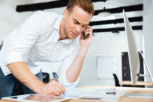 Businessman talking on cell phone and writing in office Stock photo © deandrobot
