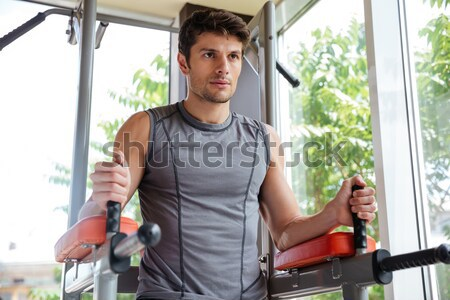 Man athlete lifting legs and working out in gym Stock photo © deandrobot