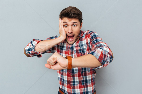 Astonished young man in checkered shirt looking at wristwatch Stock photo © deandrobot