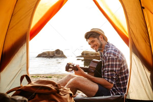Smiling young man sitting near touristic tent and playing guitar Stock photo © deandrobot