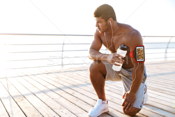 Man athlete listening to music from mobile phone in armband Stock photo © deandrobot
