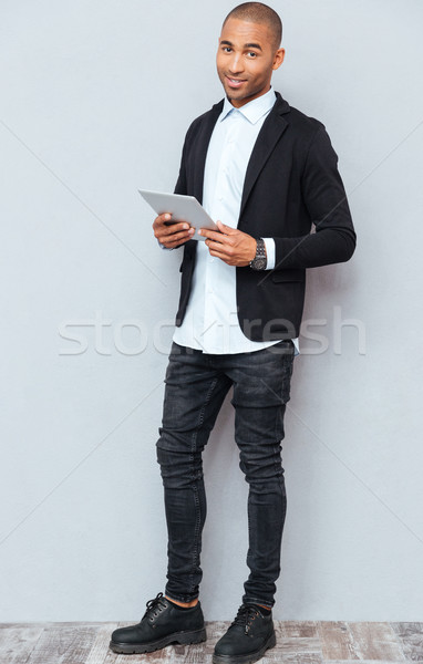Full length of smiling african american young man using tablet Stock photo © deandrobot
