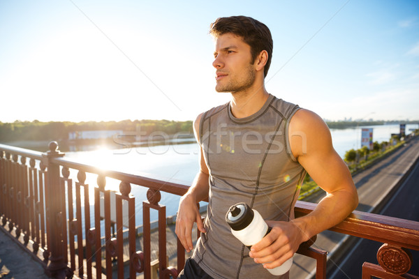 Sports man resting after running while leaning against bridge railing Stock photo © deandrobot
