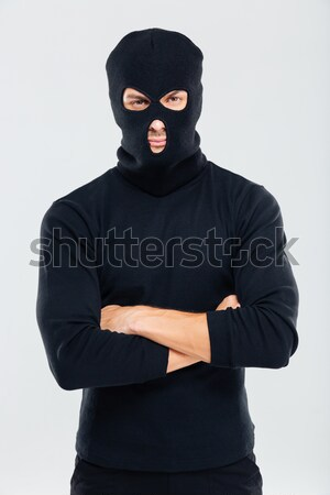 Criminal man in balaclava standing and holding gun Stock photo © deandrobot