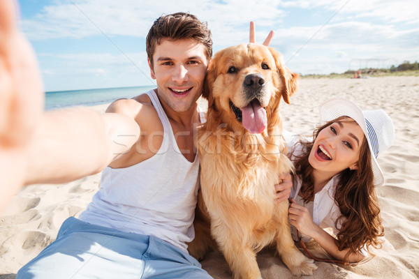 Young happy couple with dog taking a selfie Stock photo © deandrobot