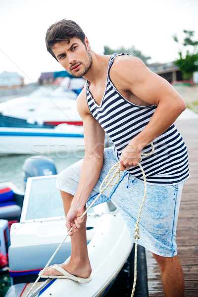 Young handsome man preparing boat to start a journey Stock photo © deandrobot