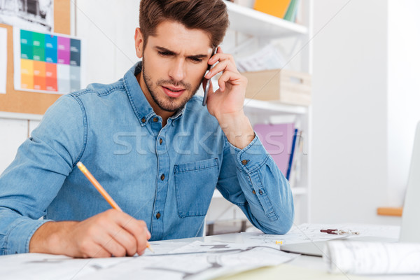 Stock photo: Pensive businessman working with documents while talking on the phone