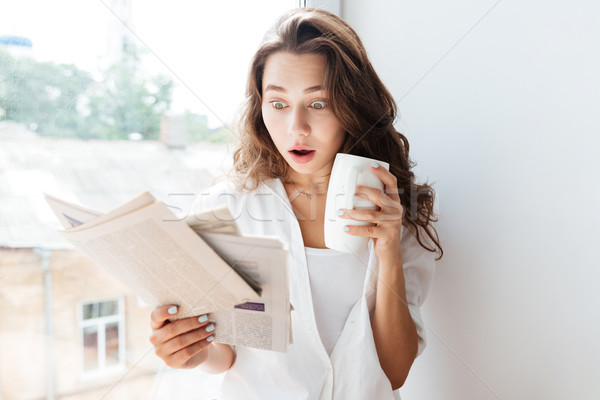 Meglepődött barna hajú nő néz újság tart Stock fotó © deandrobot