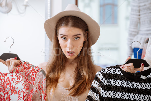 Puzzled young woman choosing clothes in clothing store Stock photo © deandrobot