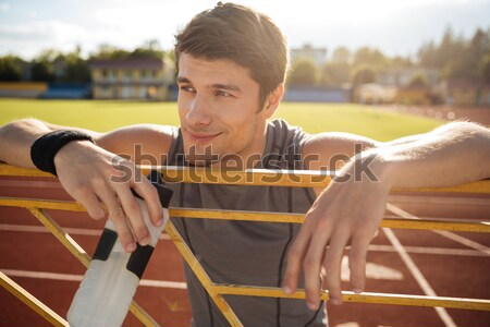Young sportsman with bottle of water leaning on the railing Stock photo © deandrobot