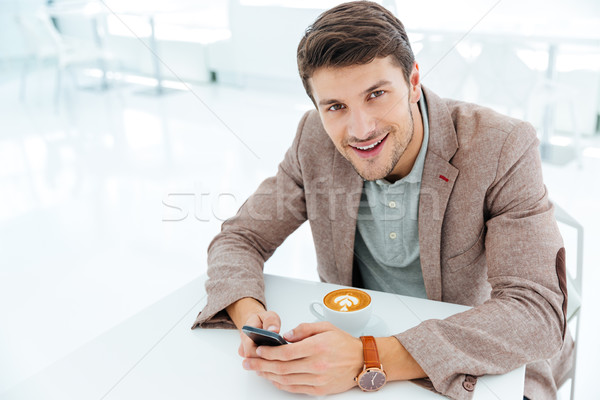 Smiling happy businessman holding smart phone and looking at camera Stock photo © deandrobot