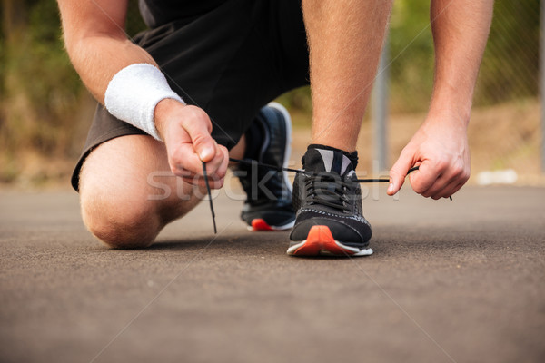 Handsome young sportsman tying shoelaces on his sneakers Stock photo © deandrobot