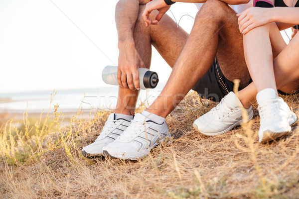Cropped image of sports couple resting while sitting on ground Stock photo © deandrobot