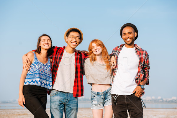 Group of cheerful people standing and embracing outdoors Stock photo © deandrobot