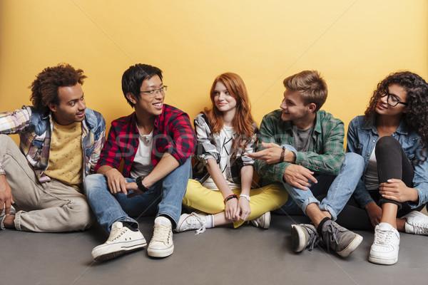 Glimlachend jongeren vergadering vloer praten Stockfoto © deandrobot