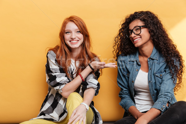Stock photo: Cheerful redhead girl sitting and showing her african american friend