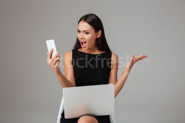 Alterar mujer gritando teléfono móvil sesión portátil Foto stock © deandrobot