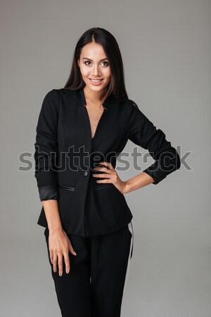Aantrekkelijke vrouw zwart pak permanente naar camera glimlachend Stockfoto © deandrobot