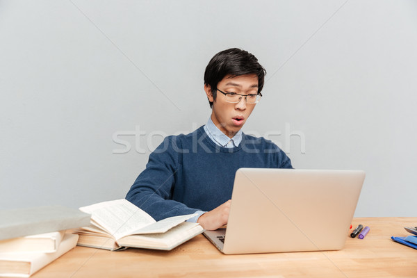 Asian student sits by the table Stock photo © deandrobot