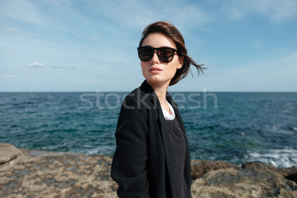 Attractive young woman standing on the seaside in windy weather Stock photo © deandrobot